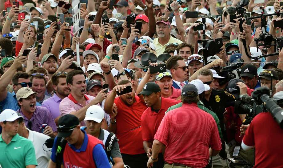 Tiger Woods, lower center, and Rory McIlroy, lower left, emerge from a horde of fans following Tiger on their way to the 18th green during the final round of the Tour Championship golf tournament Sunday, Sept. 23, 2018, in Atlanta. (AP Photo/John Amis) Photo: John Amis / Copyright 2018 The Associated Press. All rights reserved