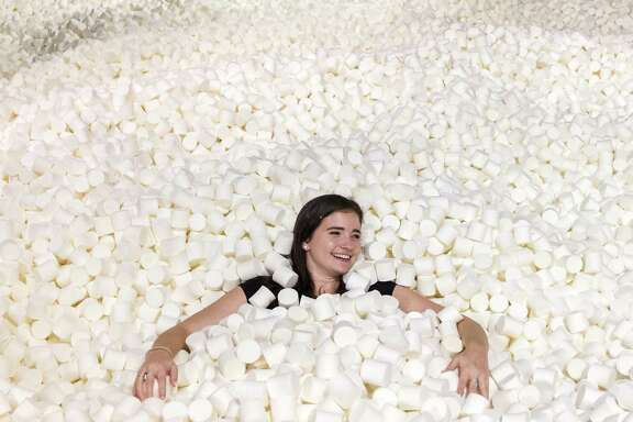 Carrie Bernstein lies in a pit filled with 250,000 marshmallows at Candytopia in San Francisco on Tuesday, September 4, 2018.