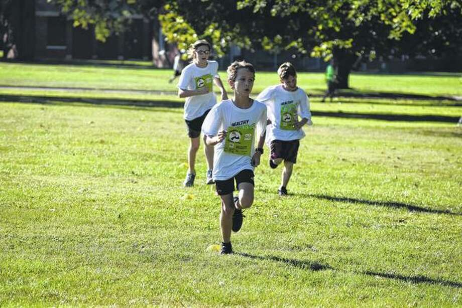 Andrew Schumacher, 9, leads the charge at the half-mile mark of the 4th to 8th grade mile at the Jacksonville Get up and Get Go! Healthy Kids Running Series Sunday. Schumacher is followed by Brody Skiles, 9, and Rachel Jensen, 11. Photo: Audrey Clayton   Journal-Courier
