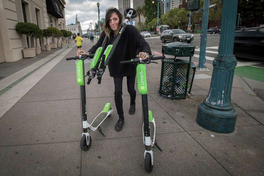 Livia Looper pushes LimeBike scooters in San Francisco on May 15, 2018. Photo: Bloomberg Photo By David Paul Morris. / © 2018 Bloomberg Finance LP