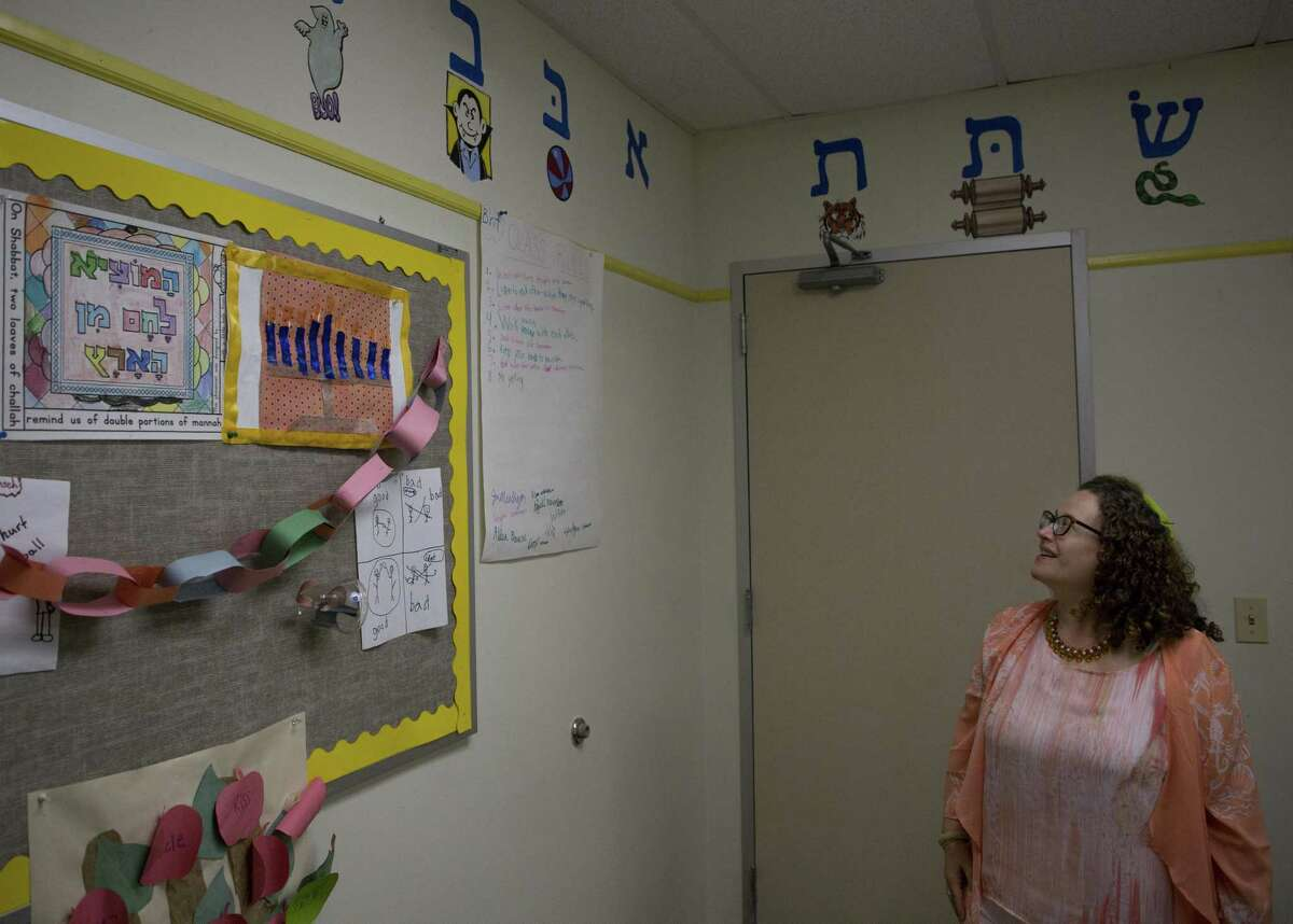 Rabbi Deborah Schloss looks up to the Hebrew alphabet that adorns the walls of the children's room at Temple Beth Tikvah Friday, Aug. 17, 2018, in Houston.