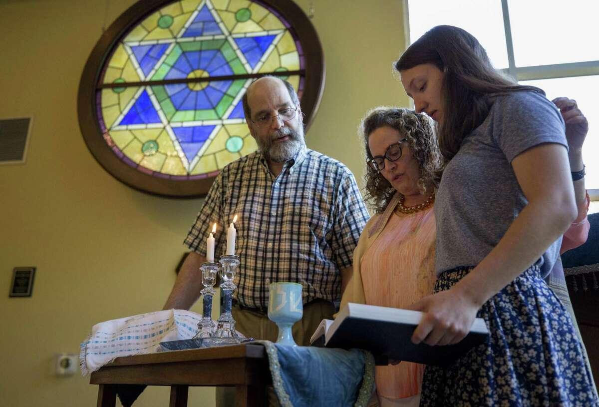 Rabbi Deborah Schloss, center, is joined by her husband, Eljay Waldman, and her daughter, Priya Schloss Fink, as they say the blessing over the lighting of Shabbat candles during the beginning of service at Temple Beth Tikvah in Houston.
