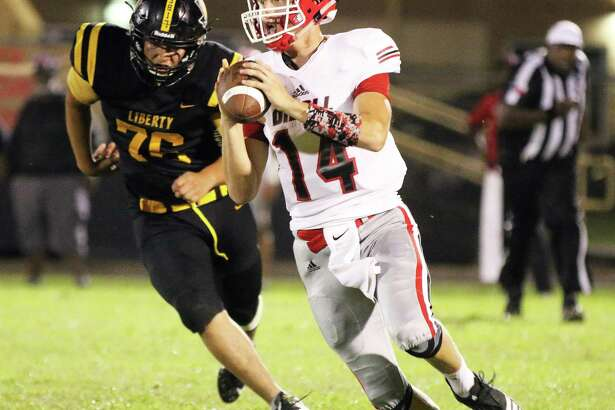 Diboll quarterback Dylan Maskunas is chased down and pressured by Liberty's Alex Pacheco before he throws an incomplete pass.