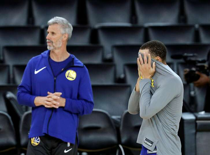 Stephe Curry (30) wipes his face with his shirt as he works out with coach Bruce Fraser during an off day practice and media day at Oracle Arena before the Golden State Warriors  play the Cleveland Cavaliers in Game 1 of the NBA Finals in Oakland, Calif, on Wednesday, May 30, 2018.