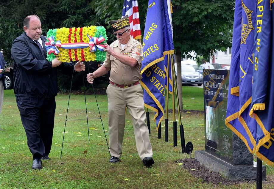 John E. Falkowski, left, manager of Green Funeral Home and Paul Schlemmer, commander of the Danbury VFW, lay a wreath in memory of the 58,300 service members killed during the Vietnam War. The Monday, Sept. 24, 2018, morning service at Rogers Park in Danbury, sponsored by the Danbury Council of Veterans and hosted by Veterans of Foreign Wars Post 149, was held on the 6th anniversary of the Traveling Vietnam Memorial War replica's visit to Danbury. The stone monument right, marks the spot where a commerative vault, holding the flowers, photos and notes left by visitors to the wall exhibit in 2012 are buried. Photo: Carol Kaliff, Hearst Connecticut Media / The News-Times