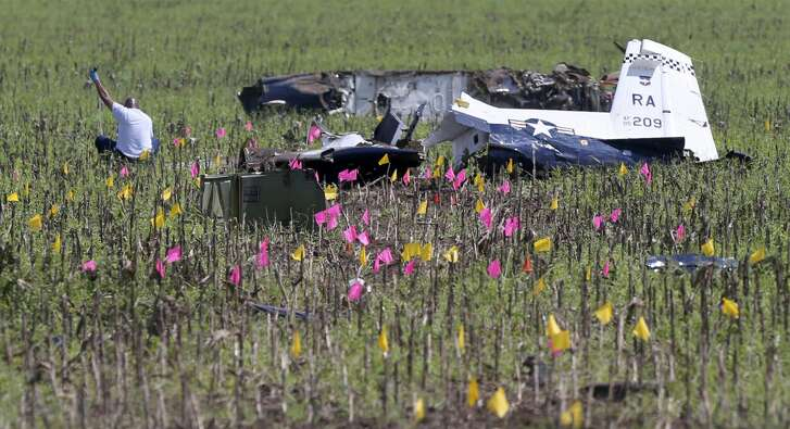 A person works Wednesday, Sept. 19, 2018 near the remains of a12th Flying Training Wing two-seat, turboprop T-6A Texan II. The airplane crashed in a field near the intersection of Nacogdoches and Evans Roads Tuesday. Both occupants of the plane ejected safely suffering only minor injuries. No one on the ground was hurt. The 12th FTW suspended flights of all T6A's while the crash is investigated.