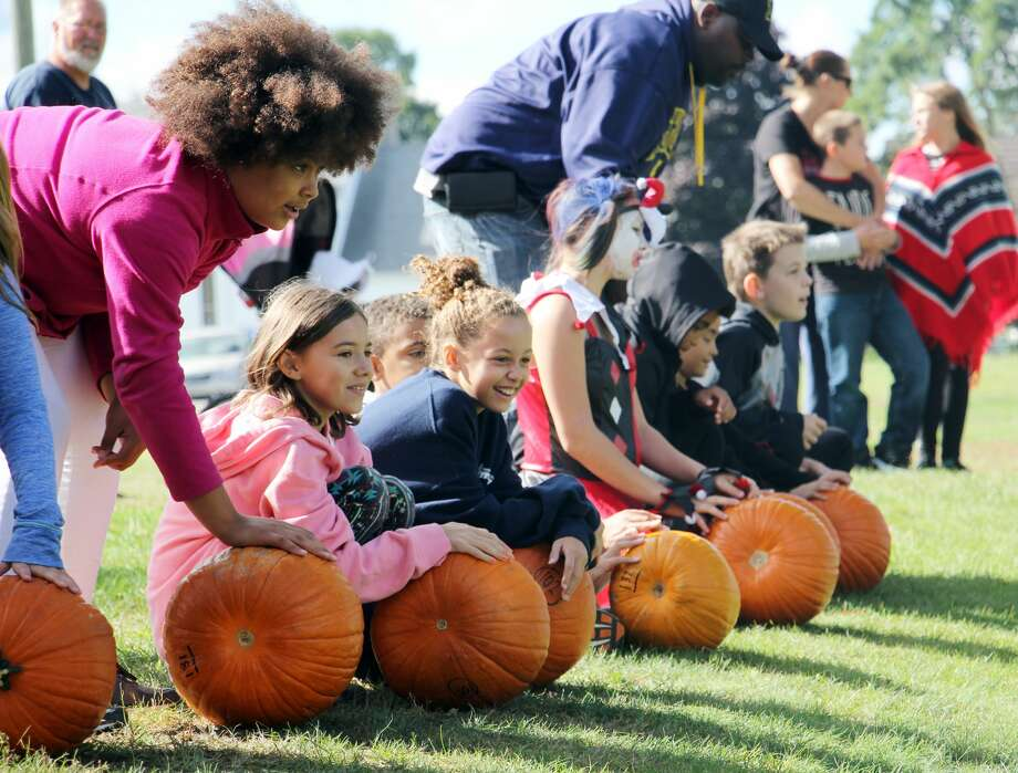 A group of pumpkin-rollers wait for the signal to shove their pumpkins down the hill at the Caseville County Park on Saturday during the city's annual Pumpkin Festival. The object of the competition was to see who could get their pumpkin to roll the farthest. Photo: Bradley Massman/Huron Daily Tribune