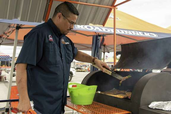 Luis Longoria, an alum of UTSA's electrical program, grills chicken, sausage and vegetables before the Roadrunners game against Texas State.