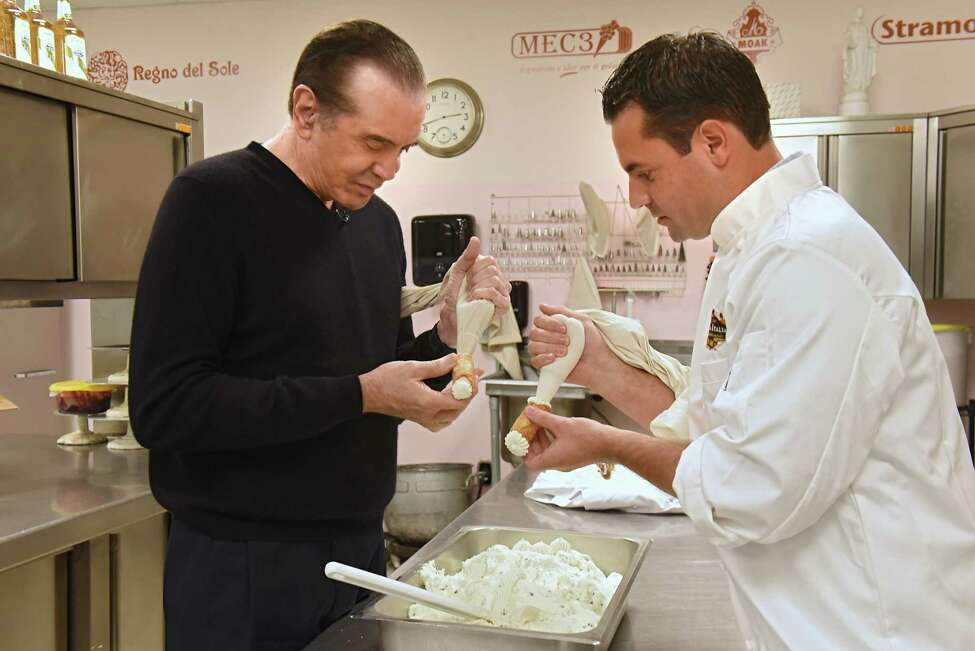Actor Chazz Palminteri, left, makes cannoli with shop owner Bobby Mallozzi at Villa Italia on Monday, Sept. 24, 2018 in Schenectady, N.Y. The cannoli making was a promotion for Palminteri's show
