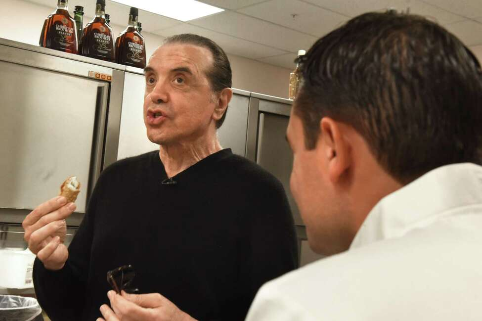 Actor Chazz Palminteri, left, tries one of the cannoli he made with shop owner Bobby Mallozzi, right, at Villa Italia on Monday, Sept. 24, 2018 in Schenectady, N.Y. The cannoli making was a promotion for Palminteri's show