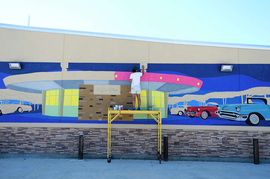 Kimberly Brown works on her mural of the iconic Pig Stand on the side of the gas station being built where the diner once stood. The mural is part of the Beaumont Convention and Visitors Bureau's downtown mural project to beautify the downtown area.  Photo taken Monday 9/24/18 Ryan Pelham/The Enterprise Photo: Ryan Pelham/The Enterprise / ?2018 The Beaumont Enterprise