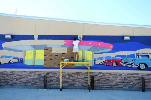 Kimberly Brown works on her mural of the iconic Pig Stand on the side of the gas station being built where the diner once stood. The mural is part of the Beaumont Convention and Visitors Bureau's downtown mural project to beautify the downtown area. Photo taken Monday 9/24/18 Ryan Pelham/The Enterprise