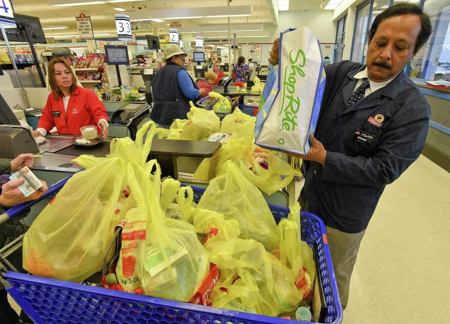 Mahabubur Kahn, a bagger at ShopRite, bags a customers order on April. 27, 2018 in non-recyclable plastic bags and reusable shopping bags. The store on Stamford's Westside is one of 11 owned and operated by Cingari family. It is hoping customers will be spurred to bring their own reusable bags as Stamford's Board of Representatives look to draft an ordinance that would prohibit the use of non-recyclable plastic bags. The store was offering a free reusable bag to shoopers this weekend. Photo: Matthew Brown / Hearst Connecticut Media / Stamford Advocate