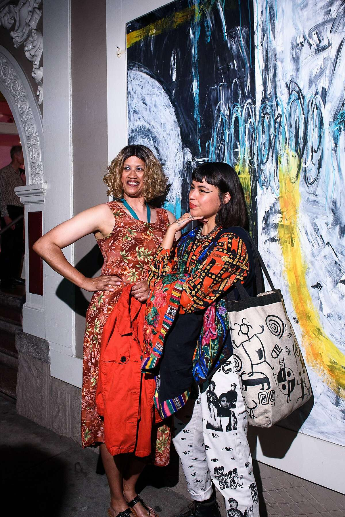 """Creativity Explored artist�Christina Marie Fong (left) and Grace Rosario Perkins posing in front of a mural by JD Green on the exterior of the Creativity Explored studio at """"Fabulate"""" the art center's Sept. 20 fashion show kicking off their exhibition up through Nov. 15 at their gallery at 3245 16th St."""