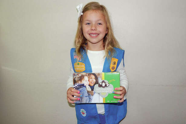 GSofSI Girl Scout Alvina Farley displays a box of Girl Scout candy.