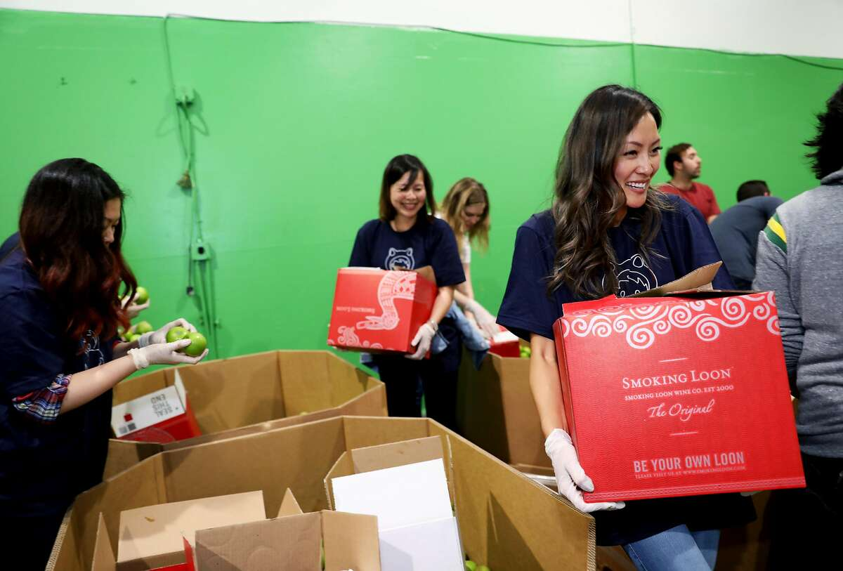 Salesforce employee Erika Ny, an operations team member, carries a packed box of Granny Smith Candy apples at the San Francisco - Marin Food Bank, located at 900 Pennsylvania Ave., in San Francisco, Calif., on Wednesday, September 19, 2018. Salesforce gives its employees a week of PTO for community service and on Wednesday, eleven Salesforce employees used two hours of that time to volunteer at the food bank.