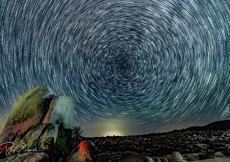 This is a star trail I created in Joshua Tree National Park. It was created by stacking 45 pictures of the same scene. The beautiful lights on the rocks were created by hikers walking through the scene with white and red lights.The glow in the background is from the town of 29 Palms, California.Thanks to @CaseyKiernan of Joshua Tree Workshops. He's a fantastic photographer who opens his bag of tricks when he teaches his photography courses.