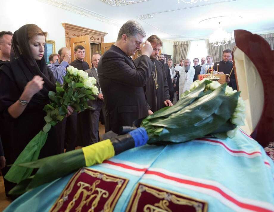 """This handout picture taken and released by the Ukrainian Presidential Press-Service shows Ukrainian President Petro Poroshenko (2nd L) and his wife Maryna crossing themselves near the coffin of Metropolitan Volodymyr, late Head of the Ukrainian Orthodox Church of the Moscow Patriarchate, in Kiev on June 5, 2014. Volodymr died at the age of 78 early on July 5. AFP PHOTO /UKRAINIAN PRESIDENTIAL PRESS-SERVICE/ MYKHAYLO MARKIV -- RESTRICTED TO EDITORIAL USE - MANDATORY CREDIT """" AFP PHOTO /UKRAINIAN PRESIDENTIAL PRESS-SERVICE/ MYKHAYLO MARKIV """" - NO MARKETING NO ADVERTISING CAMPAIGNS - DISTRIBUTED AS A SERVICE TO CLIENTS --MYKHAYLO MARKIV/AFP/Getty Images Photo: MYKHAYLO MARKIV / AFP/Getty Images / AFP"""