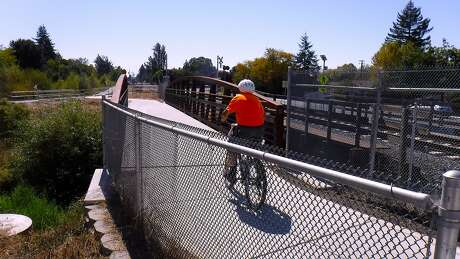 Michael Pechner rides over creek in Cotati on section of bike trail that is part of the SMART train that spans from San Rafael to Santa Rosa. About 15 miles, in a series of short sections, of the proposed 40-mile bike route is complete. Photo: Tom Stienstra, Tom Stienstra / The Chronicle