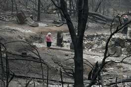 FILE - In this Aug. 9, 2018, file photo, Loretta Root wipes her eyes while visiting the remains of her home in the Keswick area burned in the Carr Fire in Redding, Calif. While California officials quickly determined an arsonist started the wildfire burning southeast of Los Angeles and that sparks from a vehicle produced the deadly wildfire in the city of Redding, causes for many of the state's worst blazes in the past decade remain a mystery. (AP Photo/John Locher, File)