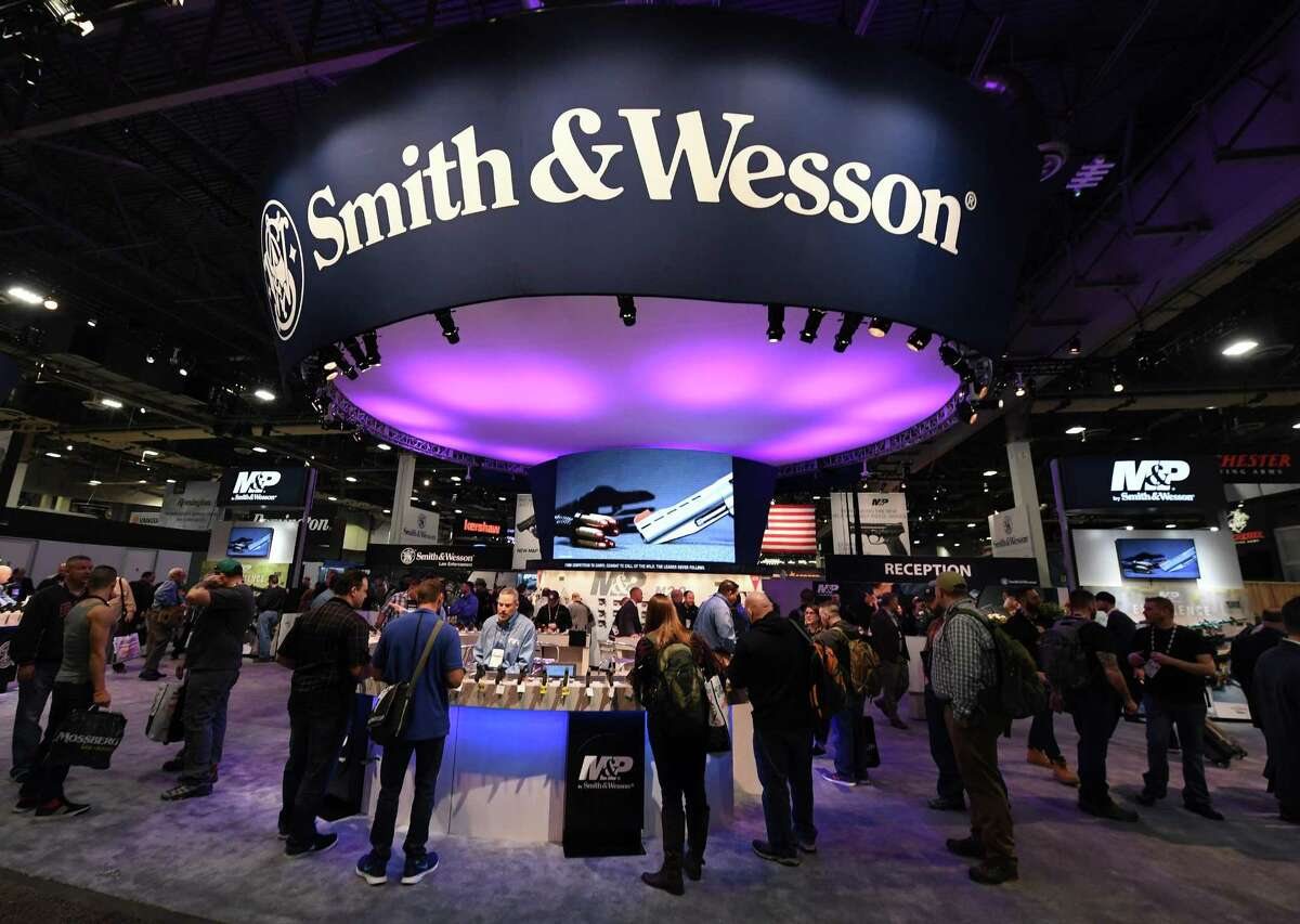 Attendees visit the Smith & Wesson booth at the 2018 National Shooting Sports Foundation's Shooting, Hunting, Outdoor Trade (SHOT) Show at the Sands Expo and Convention Center in Las Vegas.