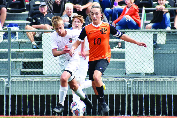 Edwardsville senior Ethan Miracle races forward with the ball past two Normal Community defenders on Saturday inside the District 7 Sports Complex.
