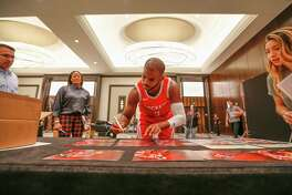 Houston Rockets guard Chris Paul (3) signs photos during their Media Day at the Post Oak Hotel Monday, Sept. 24, 2018, in Houston.
