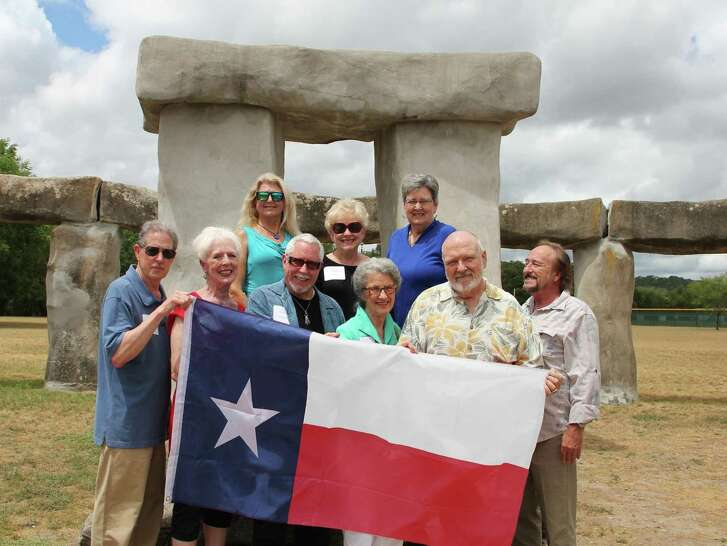"""Nine """"heritage artists,"""" all with a historical connection to the Texas Arts & Crafts Fair and the Hill Country Arts Foundation, pose in front of the Stonehenge reproduction that today lives on the foundation grounds. They are (front row, from left): John Maskey, Kathleen Cook, Steve Kriechbaum, Joyce Barton, Dusty Pendleton and Mark Jackson, and (back row) Terri McAshan, Edith Maskey and Patty Thomas. Not pictured are Daryl Howard and Fred Stockbauer."""