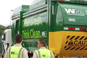 Residents in The Woodlands may see a change in their trash collection provider in 2020 if township officials cannot come to an agreement with current provider Waste Management on a new five-year contract. In this file photograph, Waste Management employees get a closer look at one of the company's new trucks that run on Clean Natural Gas during Friday's opening celebration of the company's Clean Natural Gas station in Conroe.