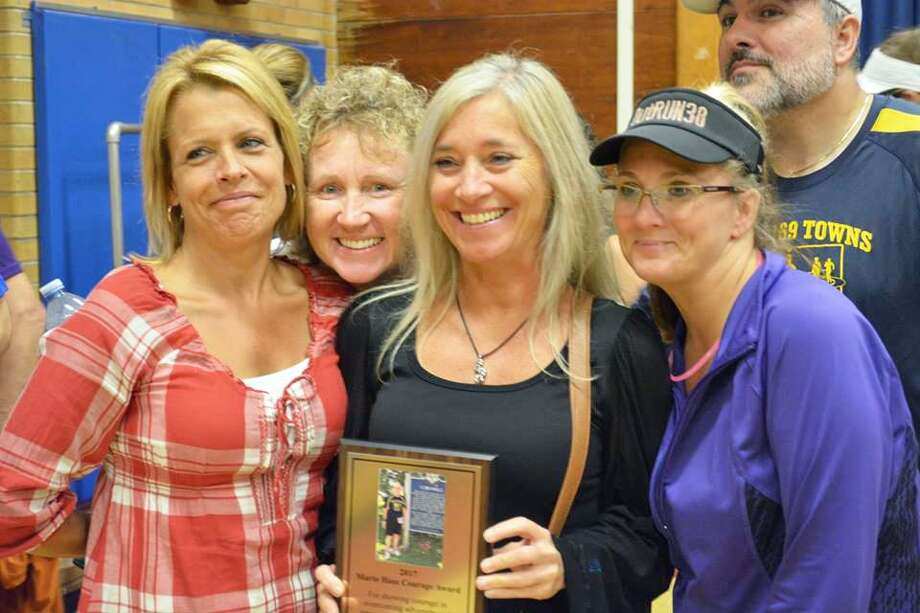 Julie Aresco of Middletown, center, is flanked by fellow Run 169ers, from left, Doreen Laliberte, Sherri Condon, and to her right, Celeste Fong and Sergio De Sousa at the ceremony during which she was presented the Mario Hasz Courage Award. Areso, who has a TBI from a work-related accident, is running the Eversource Hartford Half Marathon Oct. 13. Photo: Cassandra Day / Hearst Connecticut Media