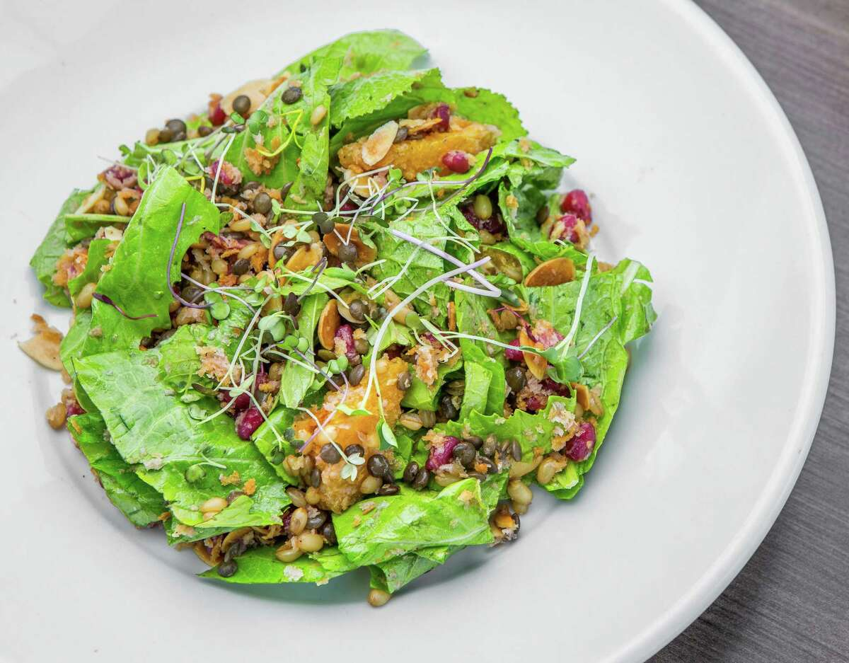 Wheatberry salad with lentils du puy, pomegranate, mustard greens, toasted almonds and orange shallot vinaigrette at Weights + Measures
