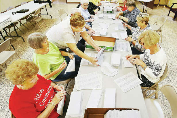 Godfrey Village Clerk Pam Whisler, center, bends over to gather up more envelopes ready for stamps during a gathering of volunteers Monday at the Village Hall to prepare a mass mailing to voters about the initiative on the November ballot to eliminate Godfrey Township.