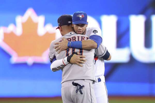 TORONTO, ON - SEPTEMBER 24: Lourdes Gurriel Jr. #13 of the Toronto Blue Jays meets with brother Yuli Gurriel #10 of the Houston Astros before the start of their MLB game at Rogers Centre on September 24, 2018 in Toronto, Canada.