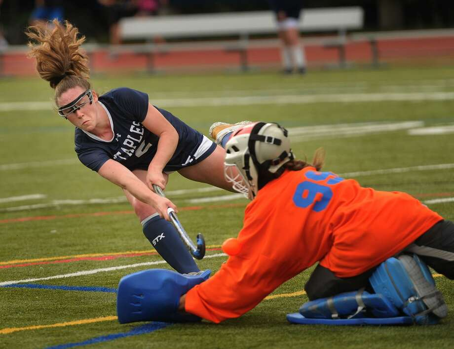 Staples' Kyle Kirby scores a goal with a shot past the shoulder of a diving Fairfield Ludlowe goalie Grace Ghee in Monday's game in Fairfield. Photo: Brian A. Pounds / Hearst Connecticut Media / Connecticut Post