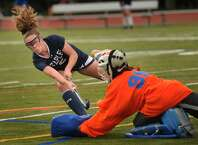Staples' Kyle Kirby scores a goal with a shot past the shoulder of a diving Fairfield Ludlowe goalie Grace Ghee in Monday's game in Fairfield.
