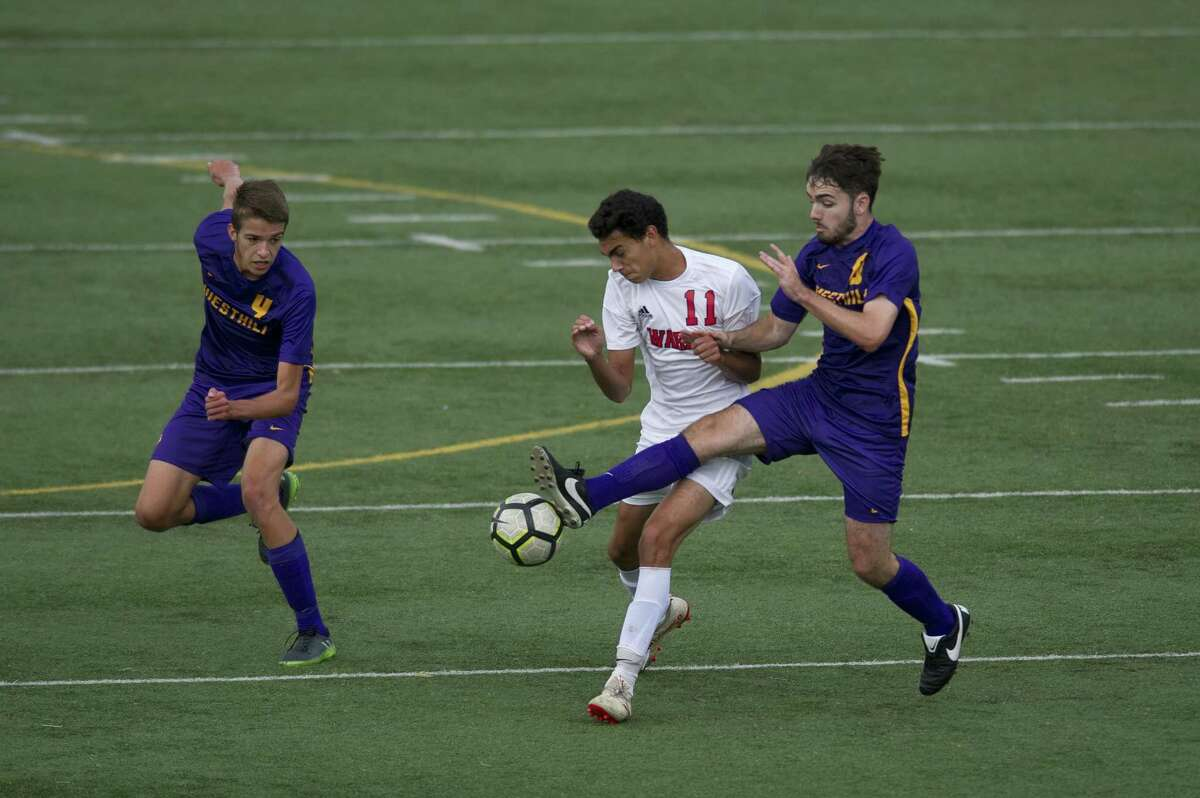 Westhill High School's Eoin Keogh stretches and takes control of the ball from Fairfield Warde junior Daniel Villalba during a varsity boys soccer game at Westhill in Stamford, Conn. on Monday, Sept. 24, 2018. Fairfield Warde defeated Westhill 3-2.