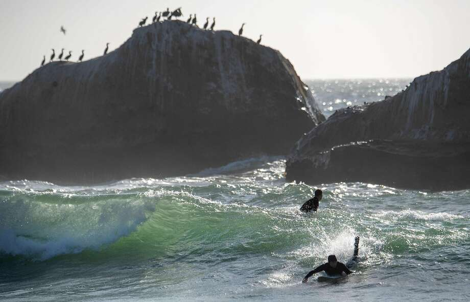A surfer catches a wave at Martin's Beach in Half Moon Bay, California on September 19, 2018. - Billionaire Vinod Khosla purchased the land and has been limiting access and charging fees to the general public in order to be able to enjoy the beach. (Photo by JOSH EDELSON / AFP)JOSH EDELSON/AFP/Getty Images Photo: JOSH EDELSON / AFP/Getty Images