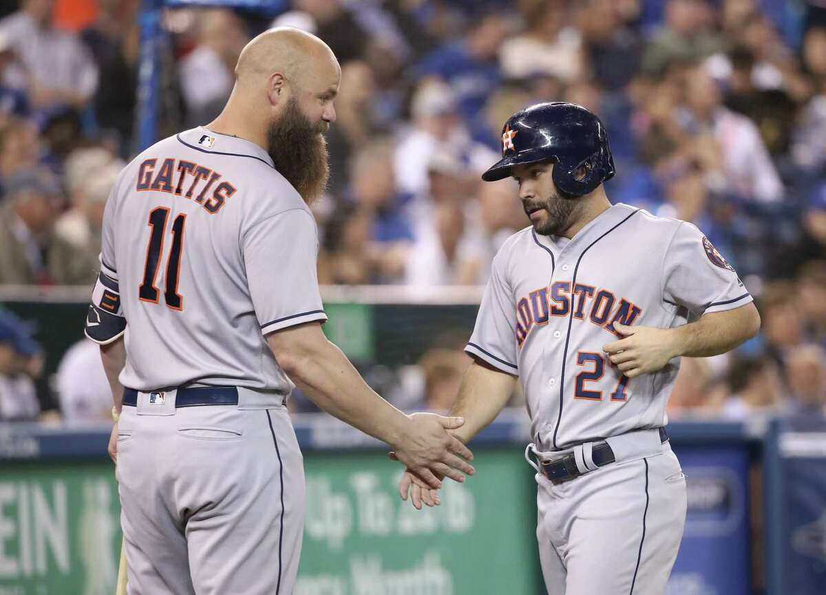 TORONTO, ON - SEPTEMBER 24: Jose Altuve #27 of the Houston Astros is congratulated by Evan Gattis #11 after scoring a run in the third inning during MLB game action against the Toronto Blue Jays at Rogers Centre on September 24, 2018 in Toronto, Canada.