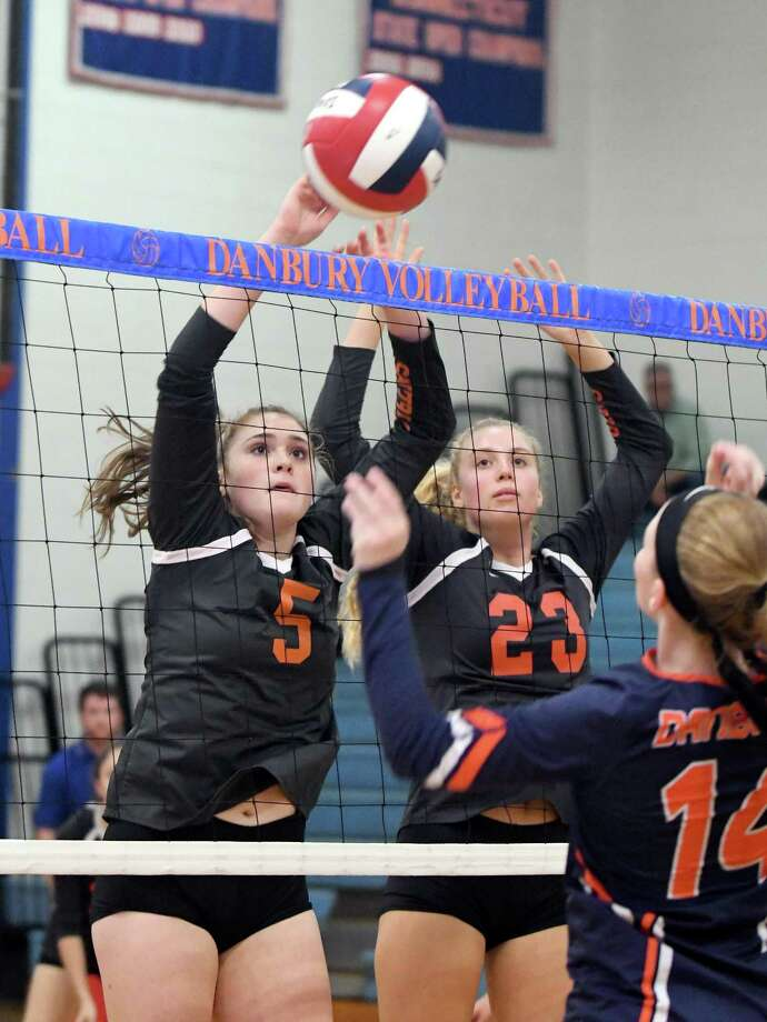 Ridgefield's Norah McNeece (5) and Katherine Garson (23) block Danbury's Shannon Quinn's spike during the Ridgefield High at Danbury High girls volleyball game, Sept. 24, 2018. Photo: Krista Benson / The News-Times Freelance