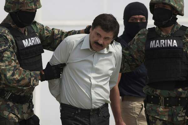 "FILE - In this Feb. 22, 2014, file photo, Joaquin ""El Chapo"" Guzman is escorted to a helicopter in handcuffs by Mexican navy marines at a navy hanger in Mexico City, Mexico. A U.S. judge has rejected a request to put off the trial of notorious Mexican drug lord Guzman. Lawyers for Guzman told Judge Brian Cogan at a hearing Thursday, Sept. 20, 2018, that they needed more time to review a mountain of evidence in the drug-trafficking case. (AP Photo/Eduardo Verdugo, File)"