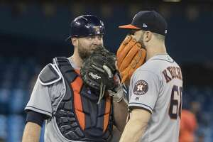 Houston Astros starting pitcher Dallas Keuchel talks to catcher Brian McCann in the fifth inning of a baseball game against the Toronto in Toronto on Monday Sept. 24, 2018. (Fred Thornhill/The Canadian Press via AP)