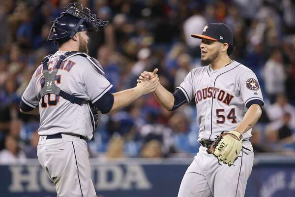 TORONTO, ON - SEPTEMBER 24: Roberto Osuna #54 of the Houston Astros celebrates their victory with Brian McCann #16 during MLB game action against the Toronto Blue Jays at Rogers Centre on September 24, 2018 in Toronto, Canada.