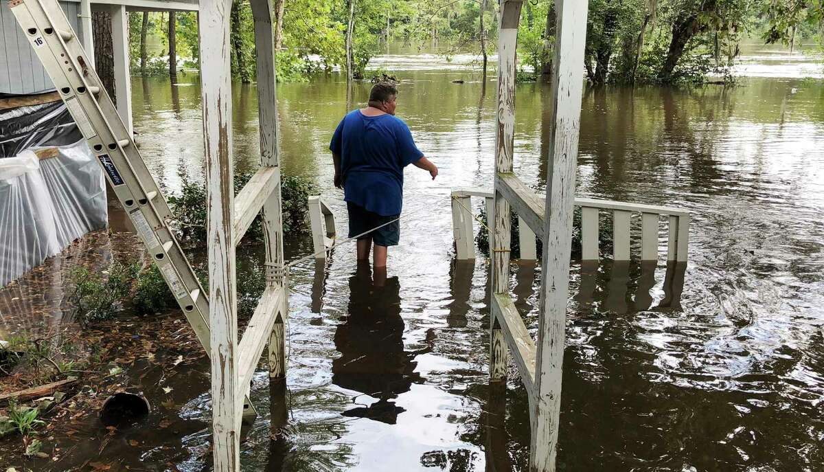Shawn Lowrimore, Pastor Willie Lowrimore of The Fellowship With Jesus Ministries', son, wades into water near the church in Yauhannah, S.C., on Monday, Sept. 24, 2018. The church is on the bank of the Waccamaw River which has already risen above its record crest and is expected to keep rising for several days, forcing thousands of evacuations in the aftermath of Hurricane Florence. (AP Photo/Jeffrey S. Collins)