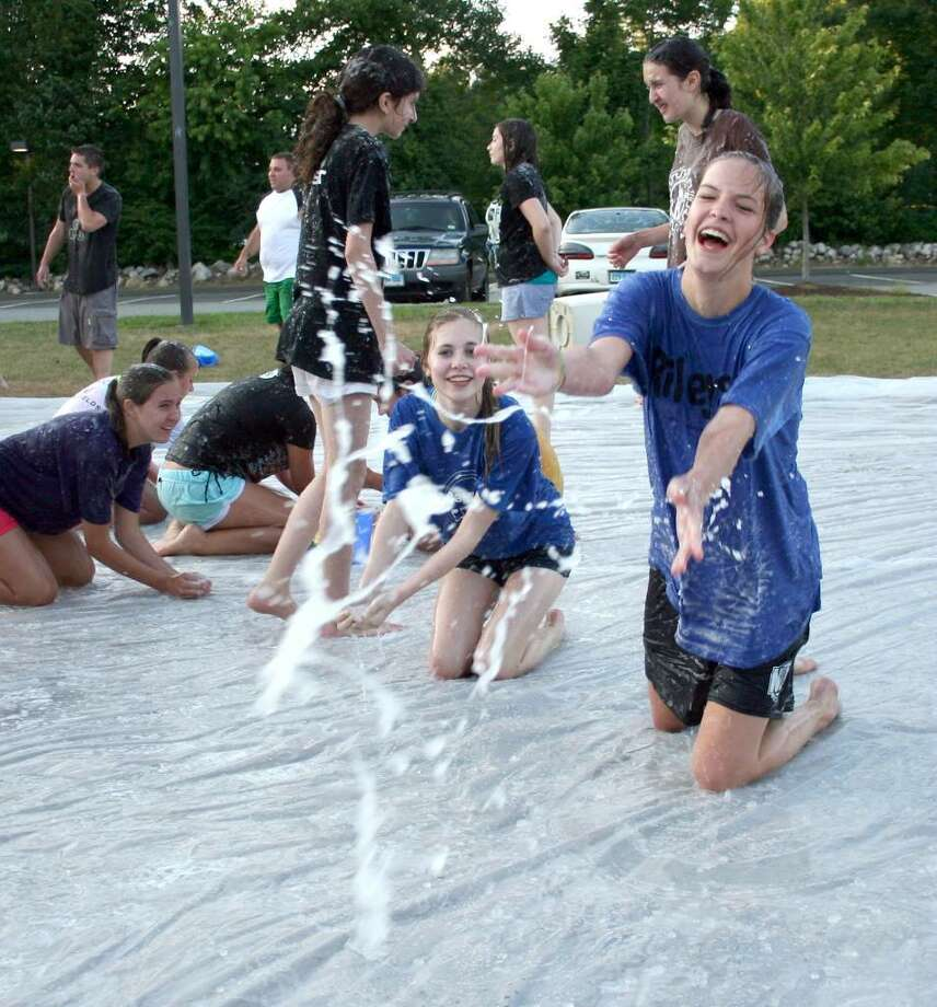 """Megan Silver, 17, of Brookfield has fun throwing slime while trying to solve a scavenger hunt clue as part of the search for """"El Grande."""" The summer-long contest is being held at the Walnut Hill Community Church in Bethel. Photo: Contributed Photo / The News-Times Contributed"""