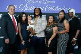 EMBARGOED FOR REPORTER UNTIL TUESDAY, SEPT. 25 Houston Texans running back D'Onta Foreman, center, stands with his family and Texans chairman and chief operating officer Cal McNair, left, and his wife, Hannah McNair, second from left, at the March of Dimes' 80th Birthday Celebration hosted by the McNair Family and Houston Texans at Steak 48 Monday Sept. 24, 2018 in Houston.