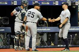 New York Yankees' Gary Sanchez, left, and Gleyber Torres (25) congratulate Brett Gardner after his leaping catch on the warning track of a fly ball hit by Tampa Bay Rays' Brandon Lowe to end the sixth inning of a baseball game Monday, Sept. 24, 2018, in St. Petersburg, Fla. (AP Photo/Steve Nesius)