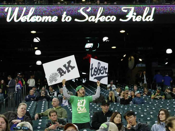 An Oakland fan celebrates just before the game between the Mariners and Oakland starts; and with Tampa Bay trailing toward the end of their game with the Yankees, clinching a wildcard spot for the A's, Monday, Sept. 24, 2018, at Safeco Field in Seattle. 207844