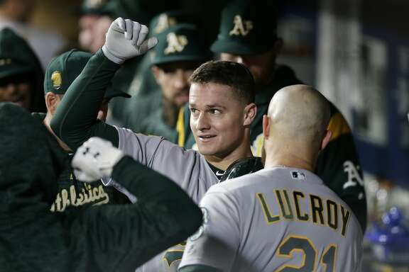 Oakland Athletics' Matt Chapman and Jonathan Lucroy celebrate in the dugout after scoring on Chapman's home run against the Seattle Mariners during the seventh inning of a baseball game, Monday, Sept. 24, 2018, in Seattle. (AP Photo/John Froschauer)