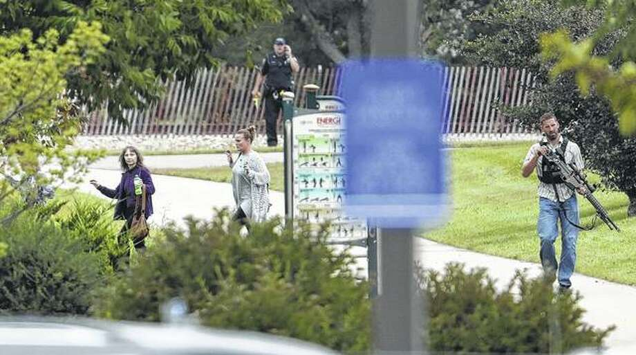 People are escorted out of a software company in Middleton, Wisconsin, where four people were shot and wounded last week. The shooter was identified as Anthony Tong, who lived in Jacksonville until about 1999. Photo: Steve Apps | Wisconsin State Journal (AP)