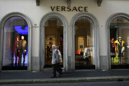 Pedestrians walk past a Gianni Versace store in central Milan on Sept. 25, 2017.